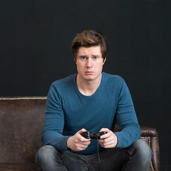 Сконцентрированный человек играя видеоигру
