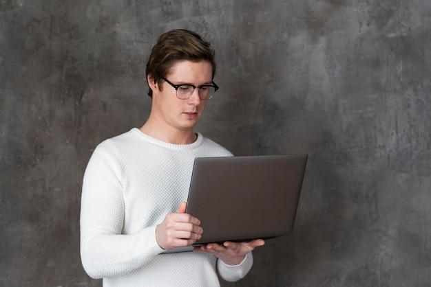 Мужчина в очках держит ноутбук