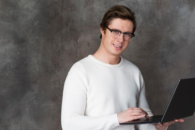 Человек в очках, подняв свой ноутбук с копией пространства
