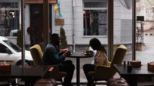 室内でコーヒーを飲んでいるロマンチックなカップル