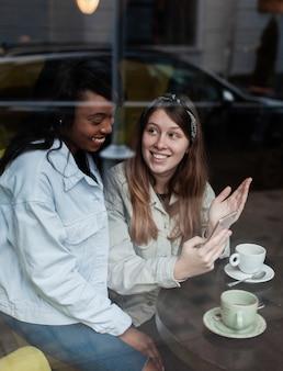 窓の近くのコーヒーを楽しむ素敵な女性