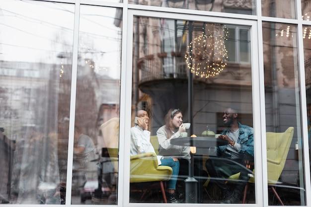 Многокультурные друзья сидят возле окна
