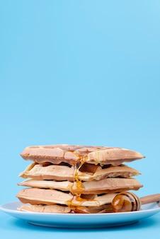 Вид спереди стопку вафель в меду с копией пространства