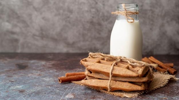 Вид спереди вафли с палочки корицы и бутылку молока