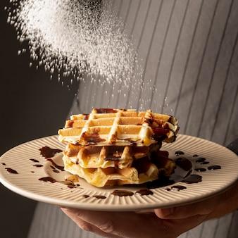 Вид спереди человека, держащего тарелку вафель и покрытия их сахарной пудрой