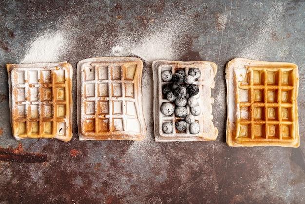 粉砂糖とブルーベリーで覆われたさびた表面のワッフルのトップビュー