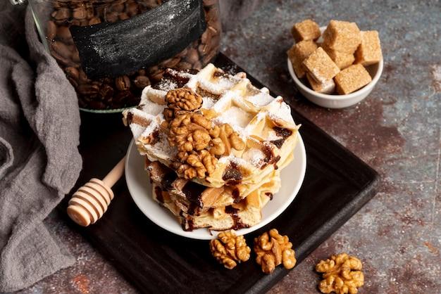 Высокий угол вафли сложены на тарелку с грецкими орехами и кусочками сахара