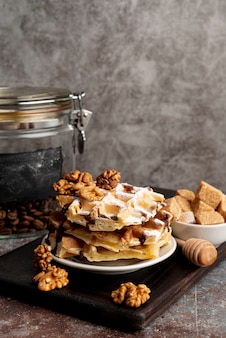 Вафли сложены на тарелку с грецкими орехами и кусочками сахара