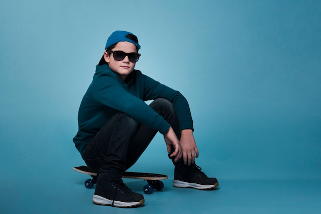 Вид спереди современного мальчика, сидящего на скейтборде