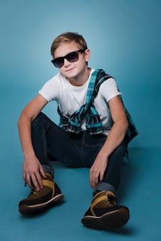Вид спереди мальчика с солнцезащитные очки позирует