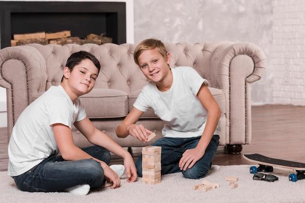 Вид спереди мальчиков, играющих в игру на полу