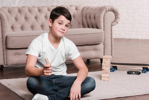 Вид спереди современного мальчика, сидя на полу
