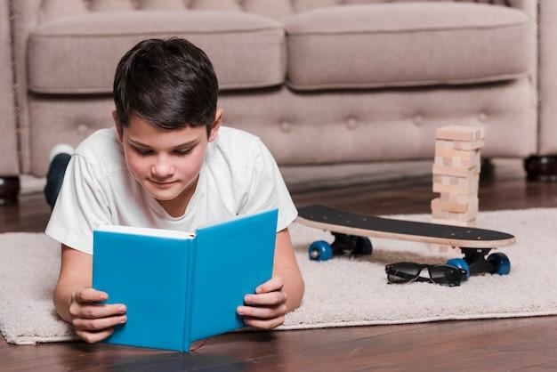 Вид спереди современного мальчика, сидя на полу с книгой