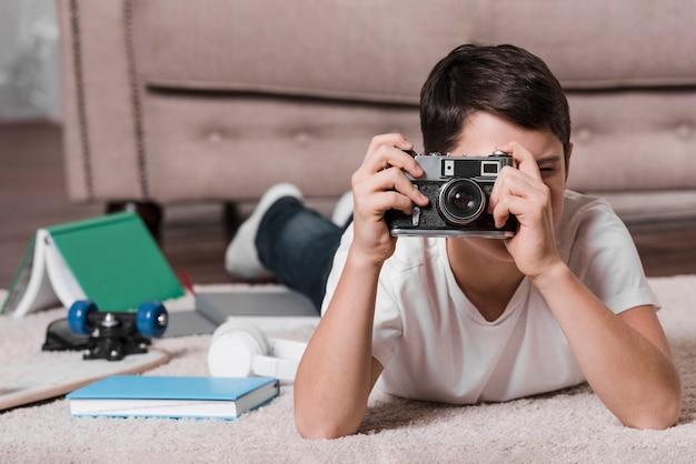 Вид спереди мальчика с фотоаппаратом