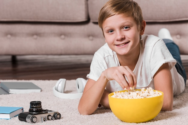 Вид спереди современного мальчика, едят попкорн