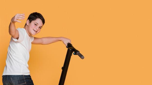 Вид спереди мальчика с скутер с копией пространства