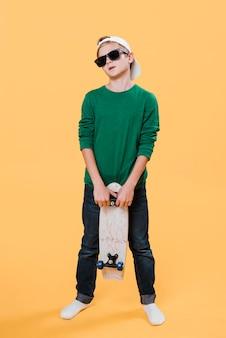 Полный снимок современного мальчика со скейтбордом