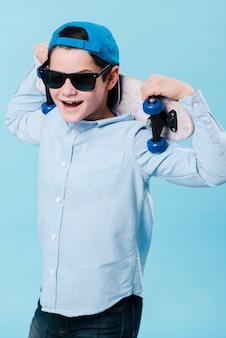 Средний снимок современного мальчика со скейтбордом и солнцезащитными очками