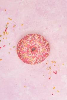 振りかけるとカラフルな艶をかけられたドーナツの平らなレイアウト
