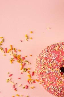Плоская кладка пончика с глазурью и разноцветными брызгами