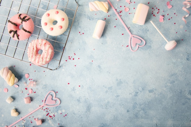 Вид сверху глазированных пончиков с ассортиментом конфет и зефира