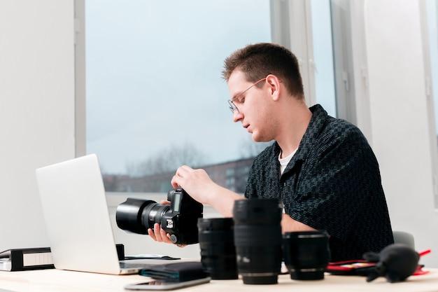 彼の机に座って働く写真家男