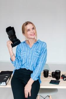 Средний снимок милой молодой женщины с фотоаппаратом