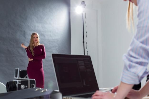 Женщина работает на ноутбуке и другая женщина позирует