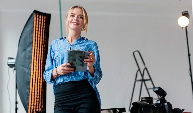 スタジオで写真傘の隣に座っているスマイリー女性