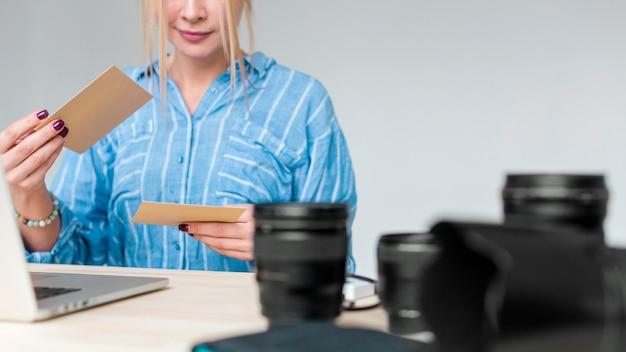Профессиональная камера объектив и женщина смотрит на фотографии