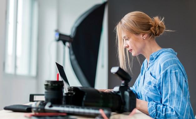 Боком фотограф женщина работает на скамейке