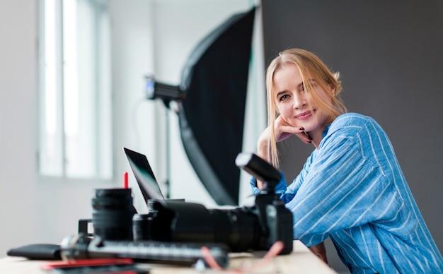 Боком фотограф женщина смотрит на свои камеры