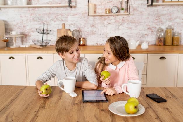 Братья и сестры вместе смотрят на свой планшет
