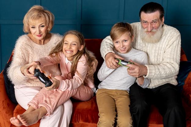 Бабушка и дедушка вид спереди играют в видеоигры со своими внуками