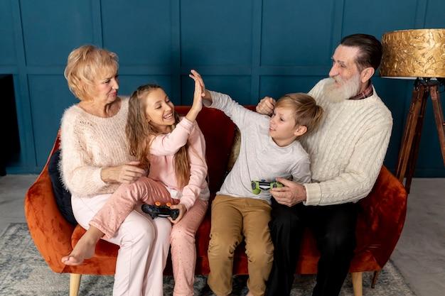 Бабушка и дедушка играют в видеоигры со своими внуками дома