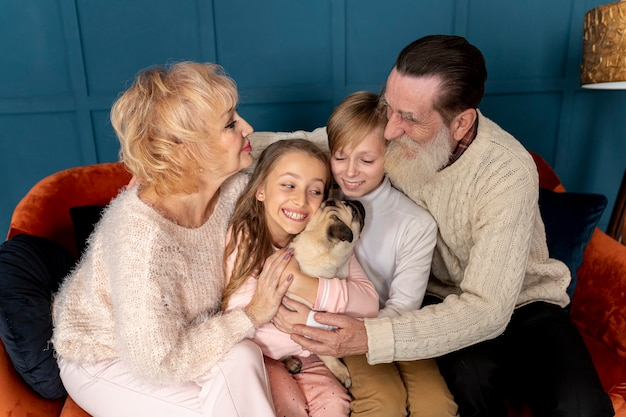 Бабушка и дедушка и внуки играют с собакой вместе