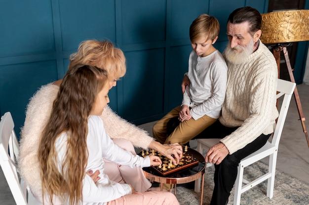 Пожилая пара играет в шахматы со своими внуками