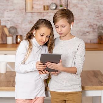 Вид спереди маленькие братья и сестры, глядя вместе на планшете