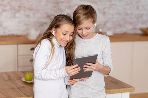 Маленькие братья и сестры, глядя вместе на планшете