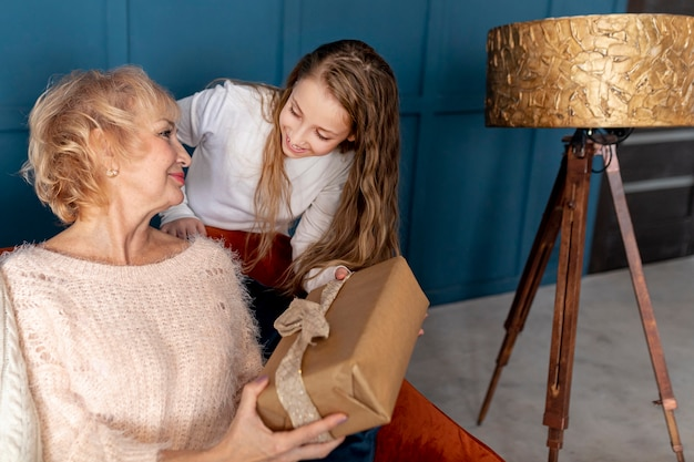 Маленькая девочка дарит бабушке подарок
