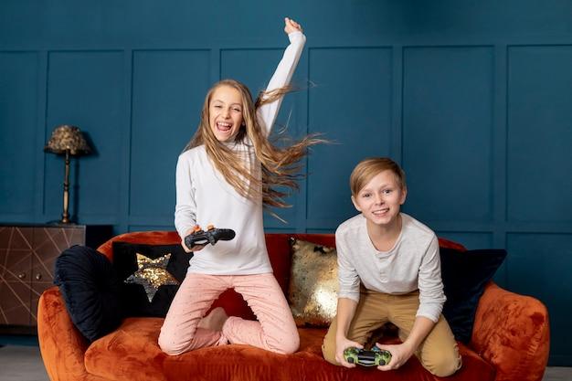 Вид спереди брат и сестра играют вместе в видеоигры