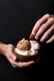 Руки крупного плана держа вкусные шарики мороженого