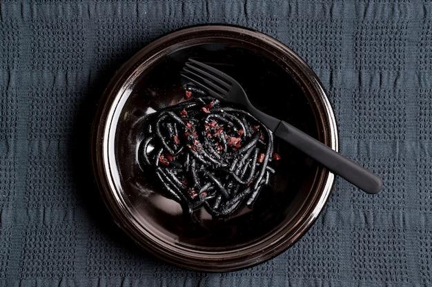 Черная паста с креветками и вилкой
