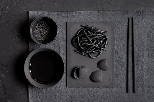 Черная паста с креветками и палочками сверху