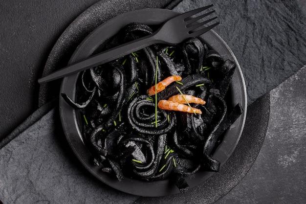 Вид сверху паста с черными креветками и вилкой