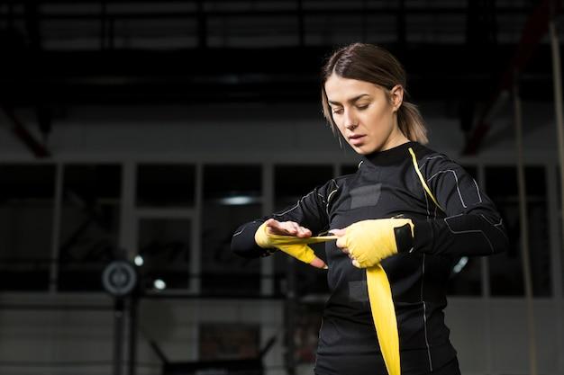 練習の準備で彼女の手を包む女性ボクサー