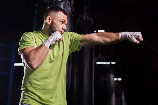ジムでパンチを投げる男性のボクサーの側面図