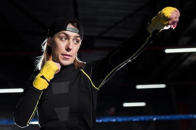 リングで練習する保護手袋の女性のボクサー