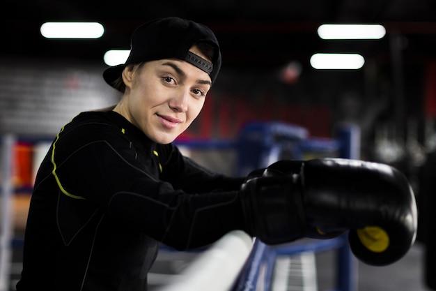 リングでポーズをとってスマイリー女性ボクサーの側面図