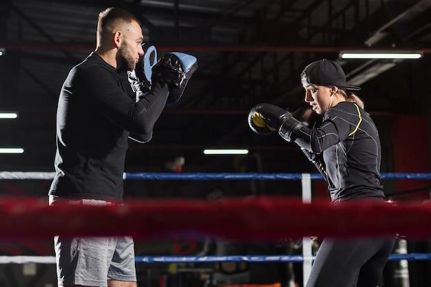 男性トレーナーとリングで練習する女性のボクサーの側面図